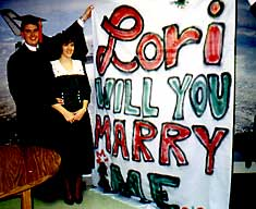 Dave proposed to Lori by holding up this big sign at his graduation!